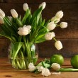 White tulips in glass vase on rustic wood - Stock Photo