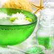 Green bowl with water and flowers ready for spa session - Stock Photo
