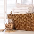 Laundry basket with linens on table — Stock Photo