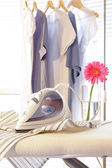 Iron on ironing board in laundry room — Stockfoto