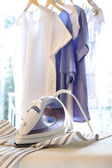 Iron on ironing board with clothes hanging — Stock fotografie