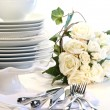 White plates stacked with utencils and roses — Stock Photo #3402284