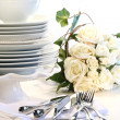 Stock Photo: White plates stacked with utencils and roses