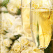 Close-up of champagne glasses with a bouquet of roses — Stock Photo #3402296