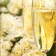 Close-up of champagne glasses with a bouquet of roses — Stock Photo