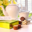 Box of chocolates on table with tea set — Stock Photo