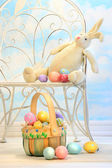 Easter bunny with eggs on chair — Stock Photo