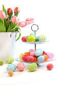 Colorful easter eggs with pink tulips on white — Stock Photo