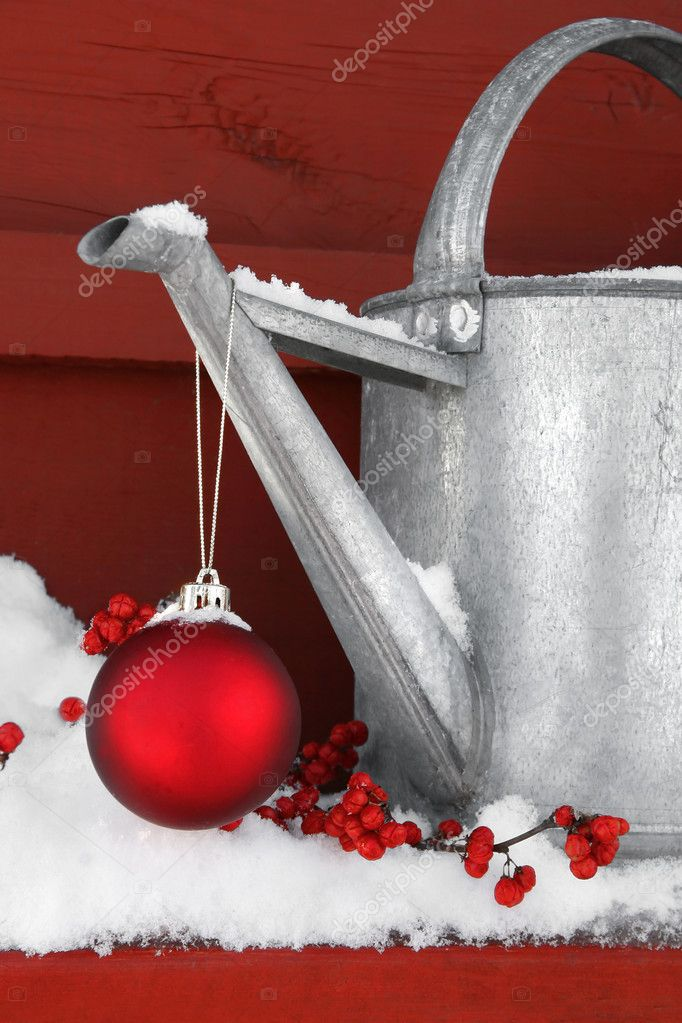 Red Christmas ball hanging on watering can in the snow — Stockfoto #3402333