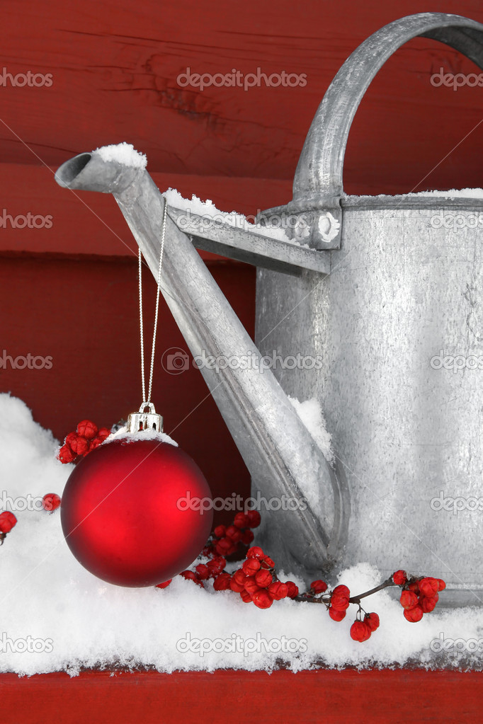 Red Christmas ball hanging on watering can in the snow — Lizenzfreies Foto #3402333