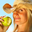 图库照片: Healthy young woman eating an apple