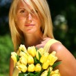 图库照片: Pretty woman holding tulips