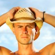 Royalty-Free Stock Photo: Young man with hat against a blue sky