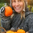 Pretty young woman holding basket of pumpkins — Foto de Stock