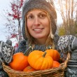 Stock Photo: Young woman holding a basket full of pumpkins