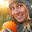 Pretty young woman holding a pumpkin — Stock Photo