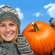 Young woman holding up a  pumpkin — Stock Photo