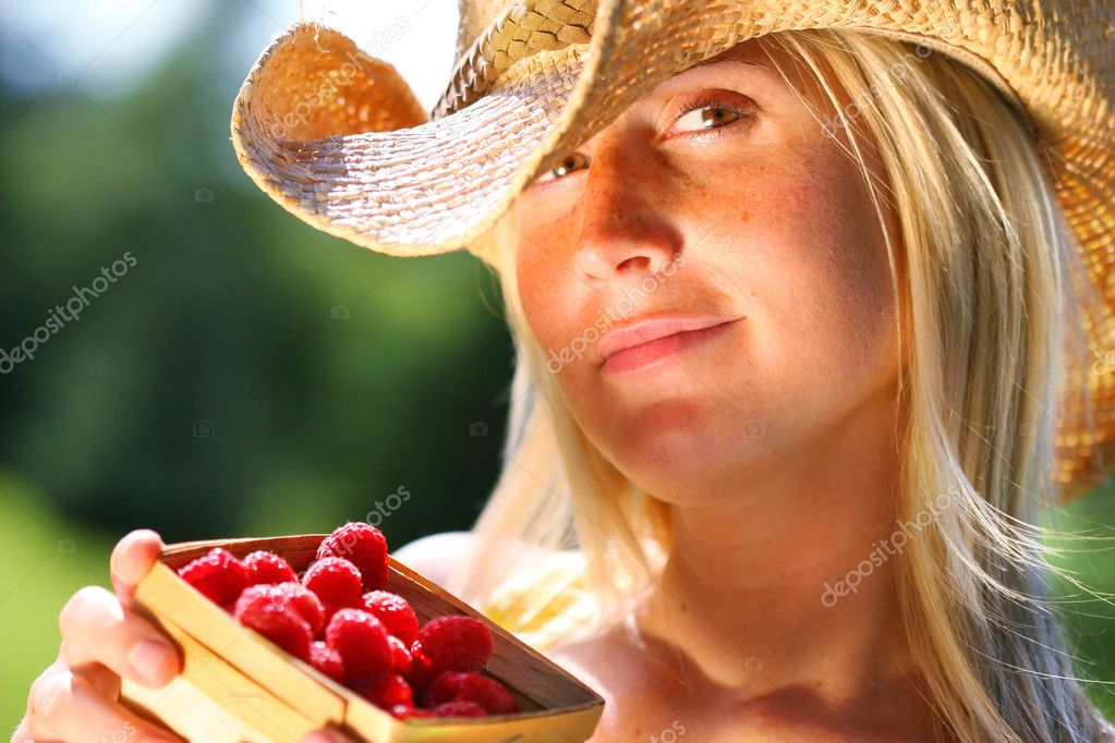 Woman showing a small basket of raspberries  Stock Photo #3450158