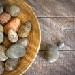 Spa rocks in wooden bowl on rustic wood — Stok fotoğraf