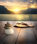 View of sandals and rocks on dock at sunset — Stock Photo