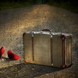 Old suitcase with red shoes left on road - Stock Photo