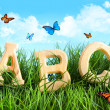 ABC letters in the grass with butterflies - Zdjęcie stockowe