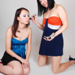 Two Chinese girls doing makeup. — Stock Photo