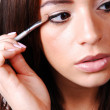Stock Photo: Young woman putting makeup.
