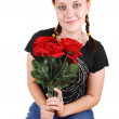 Pretty girl sitting on a chair with roses. — Stock Photo