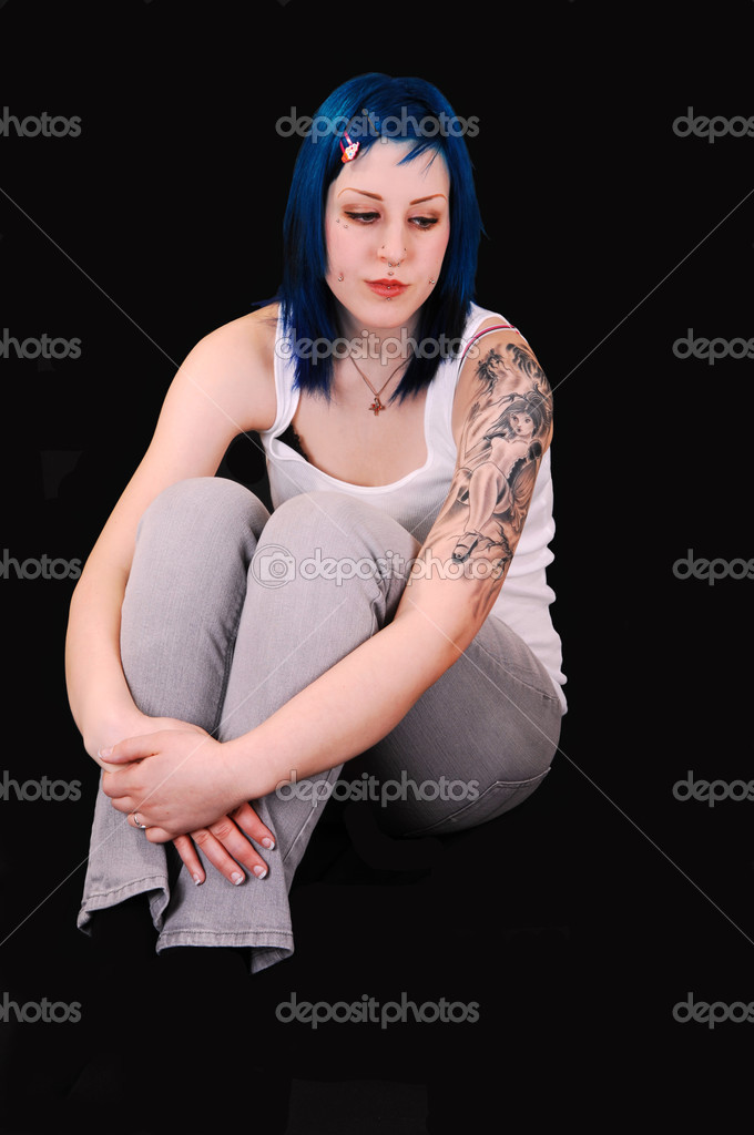 A very sad looking young girl with blue hair and a big tattoo on her leftyarm, sitting on the floor for black background. — Stock Photo #3481940