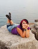 Girl lying on lakeshore. — Stock Photo