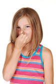 Girl holds her nose closed. — Stockfoto