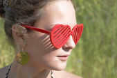 Girl smiling in red sunglasses - hearts. — Stock Photo