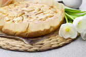 Apple pie, fork and tulips on a woven mat — Stock Photo