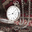 Stock Photo: Silver pocket watch on carpet