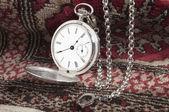 Silver pocket watch on carpet — Stock Photo