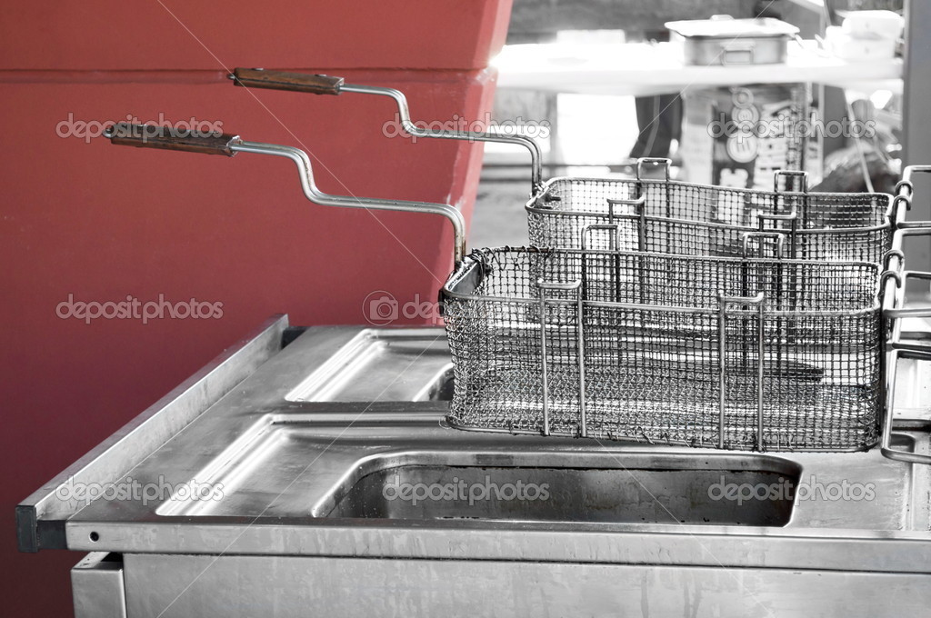 Double used restaurant fryer in open space by a red wall — Stock Photo #3509937