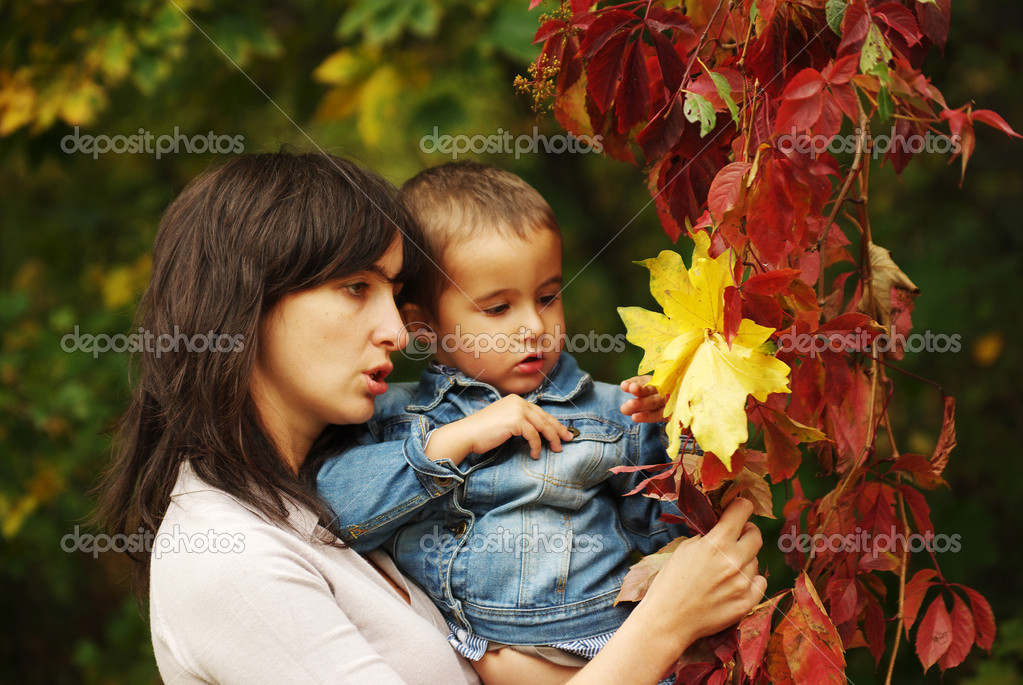 Beautiful woman and boy pick up yellow and red leaves — Stock Photo #3243484
