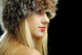 Blonde girl face closeup in fur hat with naked shoulders — Stock Photo