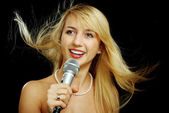 Blonde girl with naked shoulders singing karaoke — Stock Photo
