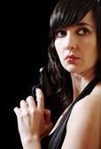 Woman in evening dress holds gun — Stock Photo