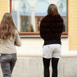 Two girls watching their reflection in storefront — Stock Photo