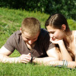 Young couple relaxing on the green meadow — Stock Photo