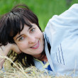 Playful woman lying on the hay - Stock Photo