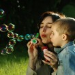 Mother and son making soap bubbles outdoors — Stock Photo #3261764