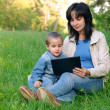Mother and son with laptop outdoors — Stock Photo