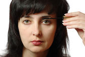 Beautiful brunette woman makes up eyelashes isolated on white — Stock Photo