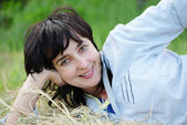 Playful woman lying on the hay — Stock Photo