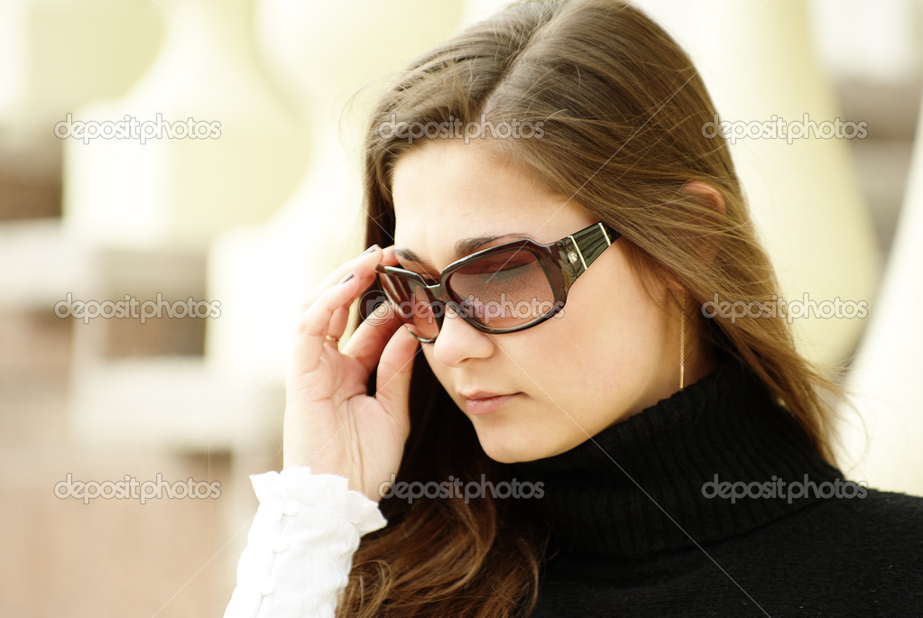 Beautiful yong girl in sunglasses by balustrade — Stock Photo #3261589