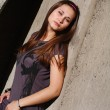 Young beautiful woman lean by the concrete wall — Stock Photo